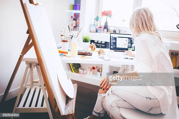 Beautiful artist responding to emails on her laptop
