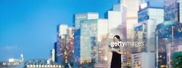 Beautiful Asian businesswoman using smartphone in financial district area in Central, Hong Kong