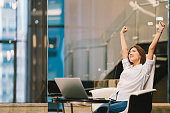 Beautiful Asian girl celebrate with laptop, hands stretch or finish work success pose, education or technology or startup business concept, modern office or living room with copy space