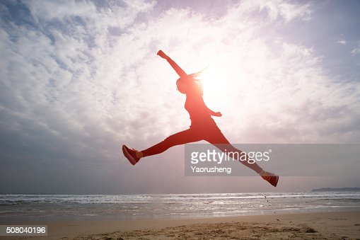 Beautiful Asian girl jumping on the beach : Stock Photo