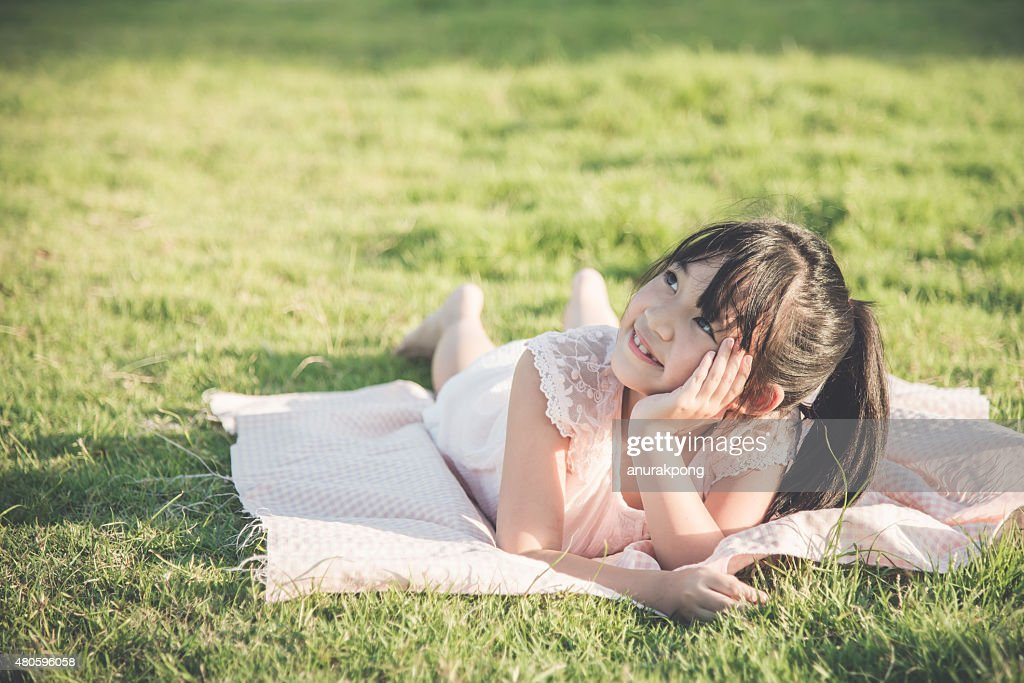 Beautiful asian girl lying and looking up on green grass : Stock Photo