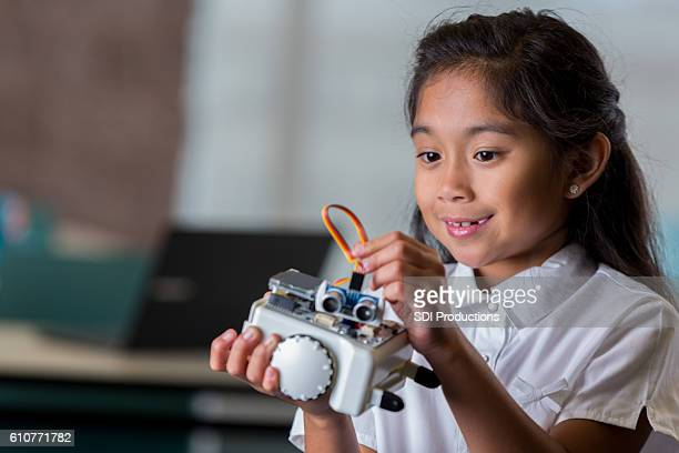 Beautiful Asian schoolgirl works with robot in technology class