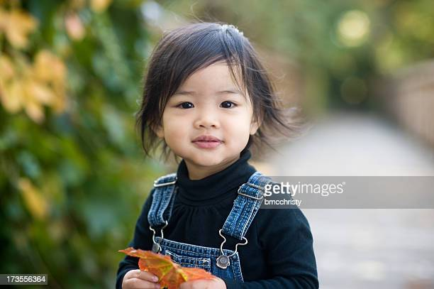 beautiful asian toddler holding leaf