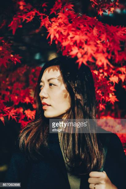 Beautiful Asian woman against Japanese red maple leaves under the sunlight