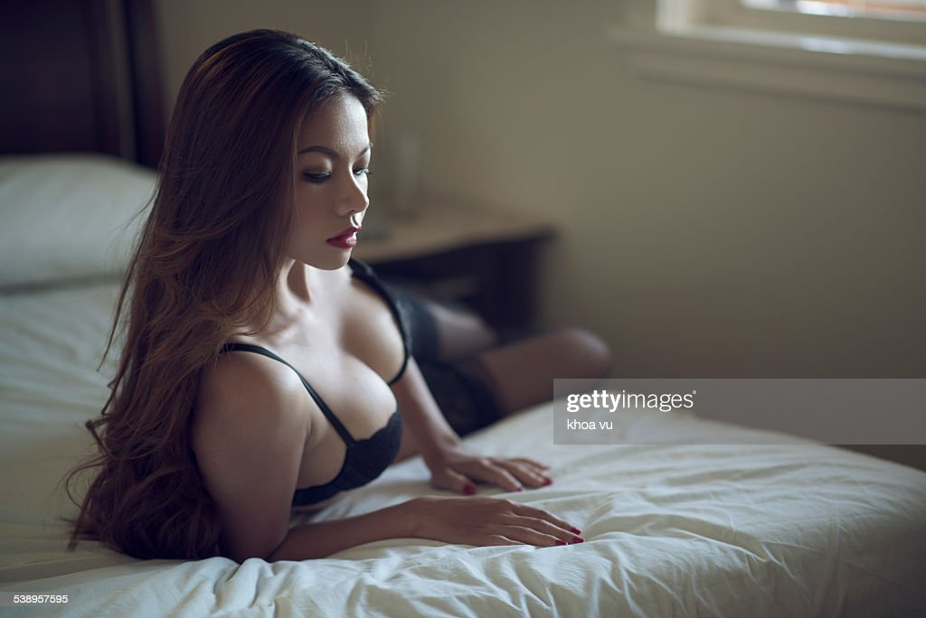 A beautiful Asian woman on a bed wearing lingerie