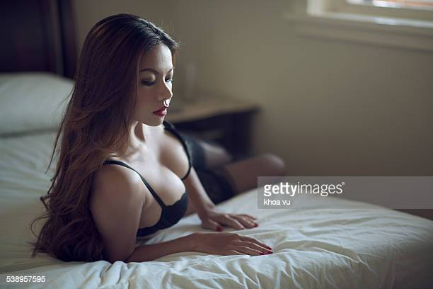 A beautiful Asian woman on a bed wearing lingerie. Seductive Women Stock Photos and Pictures   Getty Images