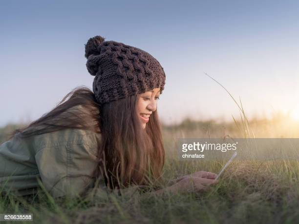 beautiful asian woman on grassfiled playing phone during sunset