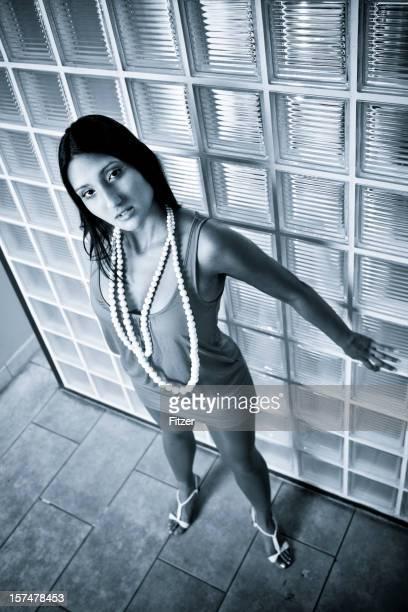 beautiful asian woman posing in front of glass bricks