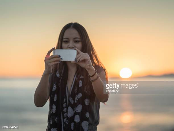 beautiful asian woman taking photo by smartphone during sunset