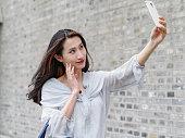 Beautiful Asian woman taking selfie using smart mboile phone.