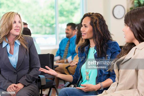 Beautiful Asian woman talks during group therapy session