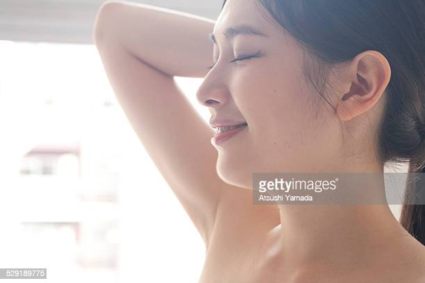 Beautiful asian woman tying her hair,smiling