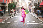 Beautiful asian woman with many shopping bags walking in the city street