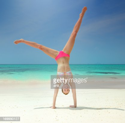 Beautiful athletic woman doing a cartwheel at the Beach