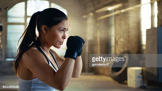 Beautiful Athletic Woman holds her Arms Ready for Defending Herself. It is a Part of Her Intensive Cross Fitness Gym Training. : Stock Photo