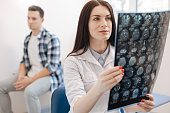 Visit to the neurologist. Beautiful attractive pleasant doctor holding an X ray photo and looking at while putting a diagnosis