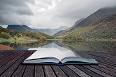 Stunning Autumn Fall landscape image of Crummock Water at sunrise in Lake District England coming out of pages of book