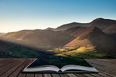 Stunning landscape image of sun beams lighting up small area of mountain side in Lake District coming out of pages of open story book
