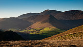 Stunning landscape image of sun beams lighting up small area of mountain side in Lake District whilst rest of area is in darkness with Robinson and Dale Head in background
