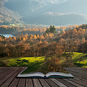 Stunning Autumn Fall landscape image of the view from Catbells in the Lake District with vibrant Fall colors being hit by the late afternoon sun coming out of pages of open story book
