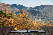 Stunning Autumn Fall landscape image of the view from Catbells near Derwentwater in the Lake District with vibrant Fall colors all around the contryside vista coming out of pages of open story book