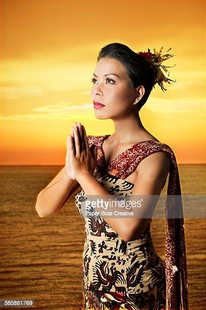 Beautiful Balinese woman standing by the sunset