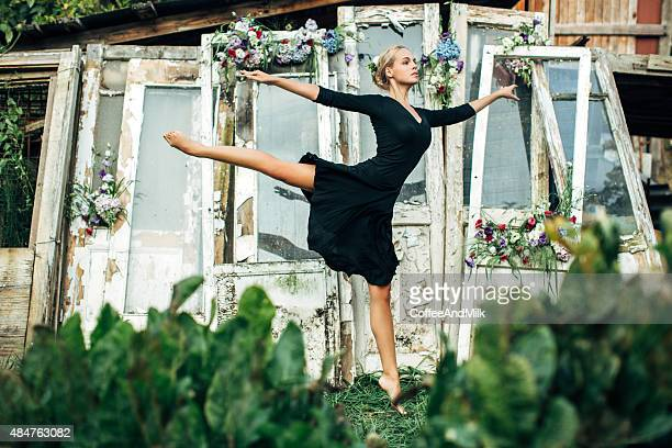 Beautiful ballerina dancing against a background of decayed doors