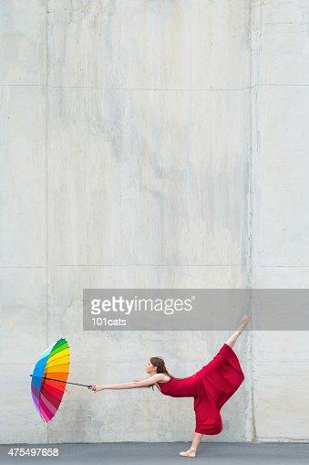 Beautiful ballerina dancing in front of concrete