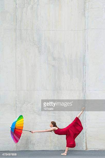 Beautiful ballerina dancing in front of concrete