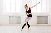 Young graceful ballerina in black at ballet class making assemble. Classical dancer in white hall practicing positions near large window, copy space