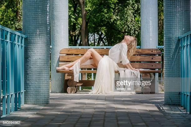 Belle femme blonde pieds nus reposant sur le banc dans le belvédère