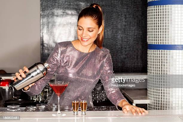 Beautiful Bartender Pouring Cocktail Into Martini Glass At Count