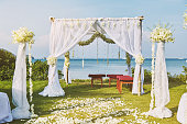 The beautiful wedding venue setting with flowers, floral decoration on arch with panoramic ocean view in background