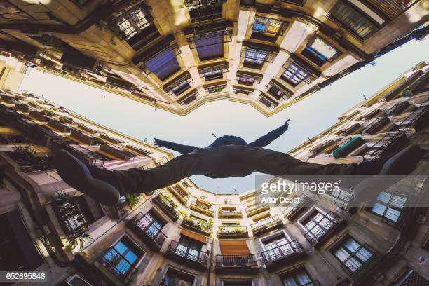 Beautiful below view with wide angle lens taken from the ground and looking up of guy jumping in the beautiful streets of gothic quarter in Barcelona city with narrow street and nice round square.