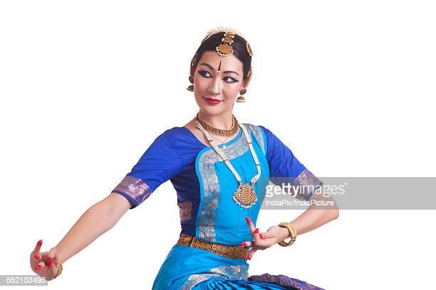 Beautiful Bharat Natyam dancer performing over white background