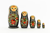 Beautiful black russian nesting dolls (matryoshka) dolls with white, green and red painting in front of dark background