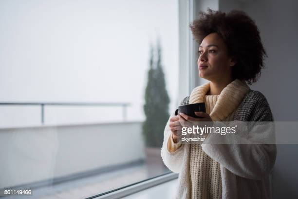 Beautiful black woman enjoying in coffee time and looking through the window.