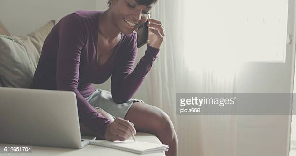 Beautiful black woman working on laptop at home