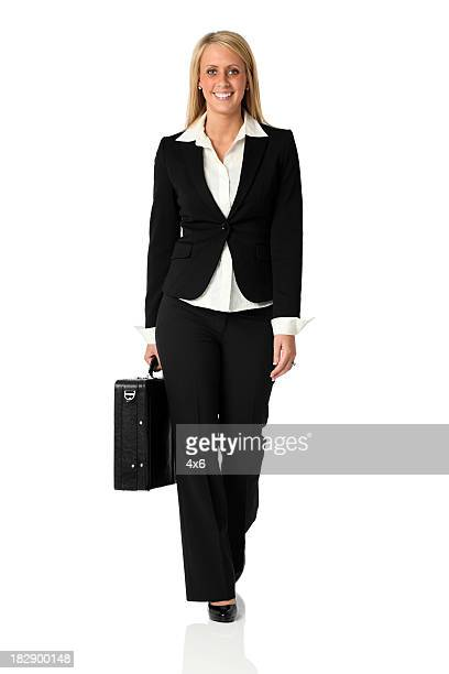 Beautiful blond businesswoman walking towards camera with briefcase
