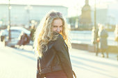 happy blond girl in leather coat looking back over shoulder on city street smiling under sun rays toned image
