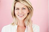 Beautiful blond woman in pink studio, smiling