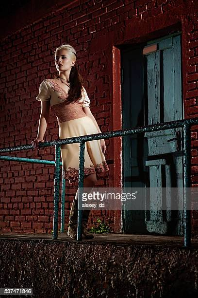 Beautiful blond pensive woman standing near red brickwall