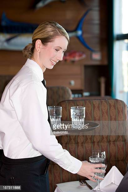 Beautiful Blond Restaurant Waitress Serving Water at Table, Copy Space