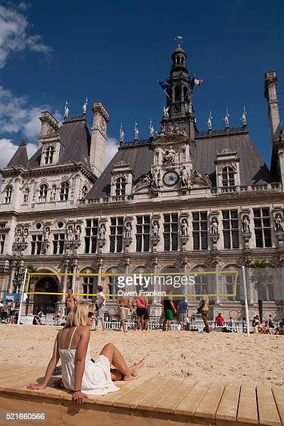 beautiful blond watching men plmay volleyball in front of Paris' Hotel de Ville,