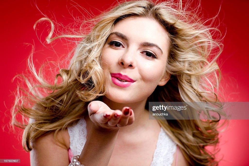 Beautiful blond woman blowing a kiss
