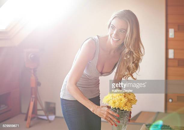 beautiful blond woman putting flowers on the table