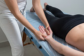 Beautiful blond woman receiving Shiatsu Treatment from a therapist.