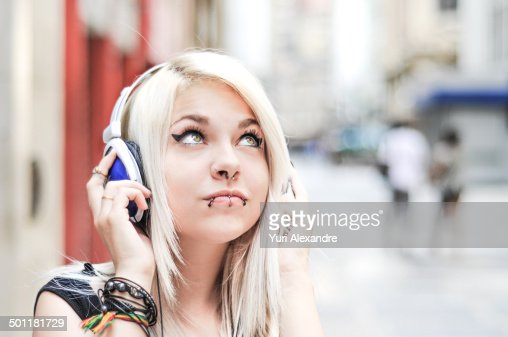 Beautiful blond young girl using headphones
