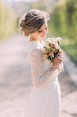 Beautiful blonde bride with bouquet of spring flowers outdoor.
