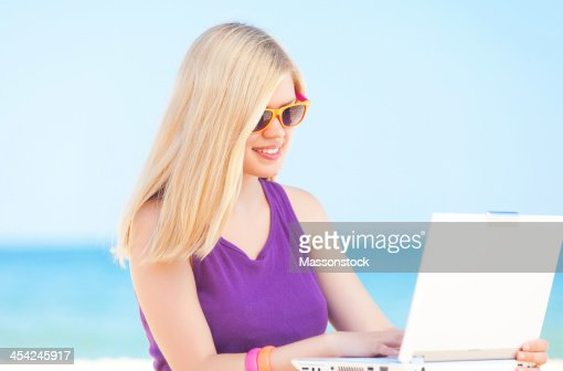 Beautiful blonde girl at the beach with laptop : Stock Photo